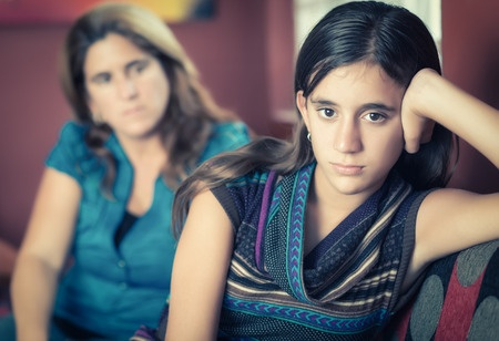31052790 - teenager problems - defiant teenage girl after a fight with her worried mother looking at her