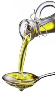 10928972 - olive oil poured from a bottle on a metal spoon. image isolated on a white background.