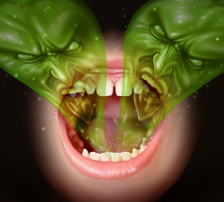 19265940 - bad breath as garlic smell eminating from inside a human mouth as a health concept of an offensive foul odour caused by smoking or eating with a green gas shaped as evil faces over an open human mouth