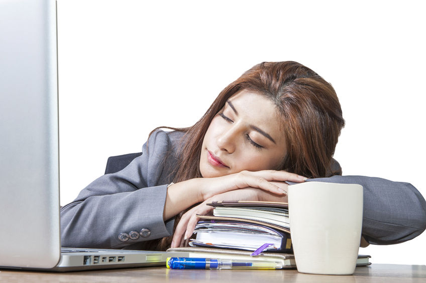 28831941 - business woman sleeping on laptop taking a power nap during work isolated